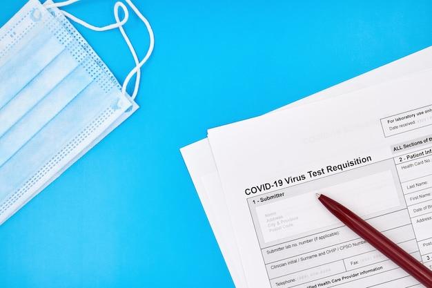 概念的な写真。顔の保護用のマディカルマスクとcovid-19ウイルステストの申請フォーム(青色の背景にペンを使用)。閉じる。