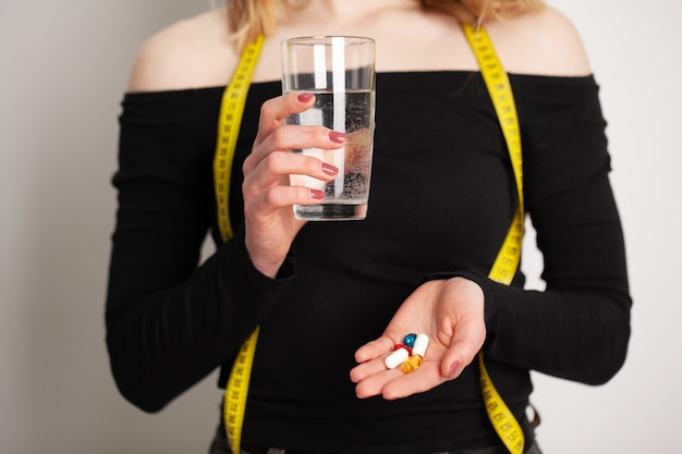 Conceptual photo of a female nutritionist holding a pill.