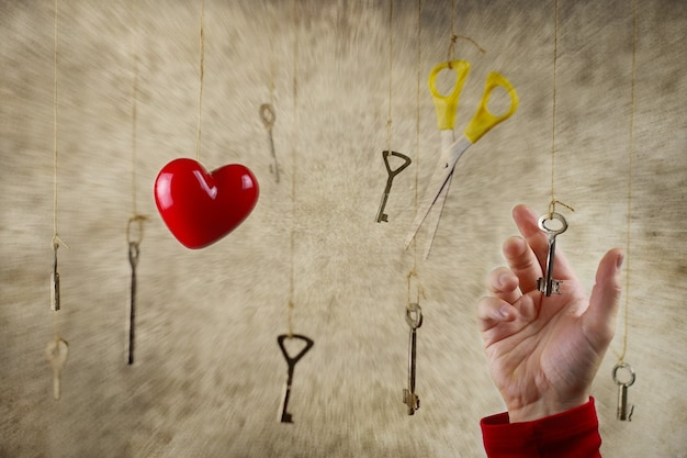 Концептуальное фото рука тянется к одному из множества старых старинных ключей, висящих на нитках