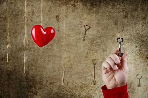 Концептуальная фотография руки, тянущейся к одному из множества старых винтажных ключей, висящих на нитках