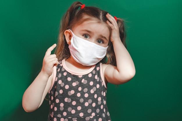 Концептуальное фото маленькой девочки в медицинской маске, показывающей указательный палец на зеленом фоне крупным планом 2020
