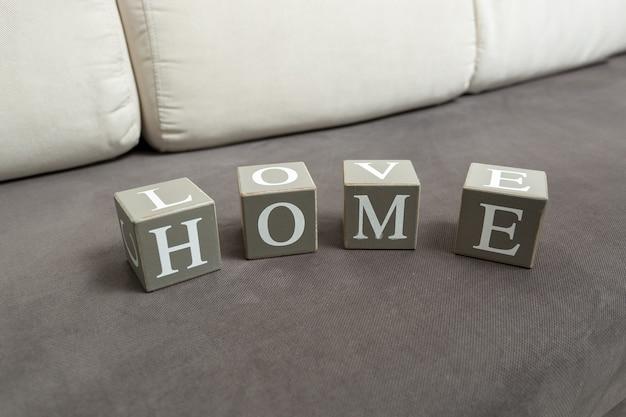 Концептуальное фото слова дом и любовь, написанное на игрушечных кирпичах