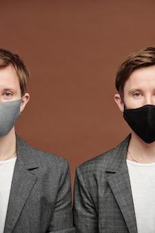 갈색 배경에 서 있는 얼굴 마스크를 쓴 어린 쌍둥이의 개념적 사진