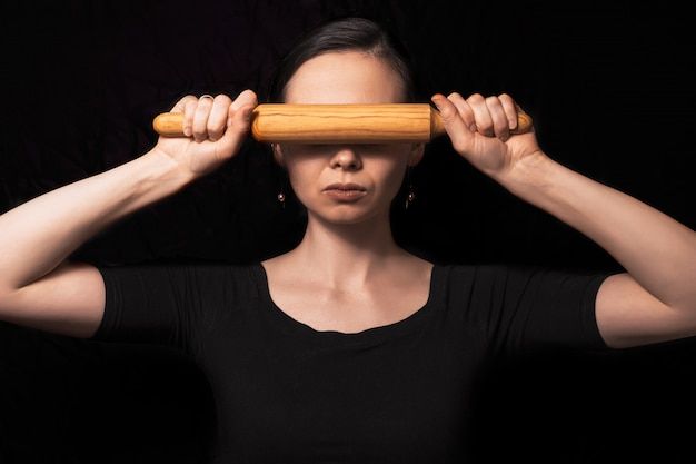 Conceptual photo with a girl and a rolling pin. girl closes her mouth with a rolling pin. a woman in an everyday household routine. helping defenseless women in families
