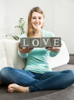 Conceptual photo of woman holding word