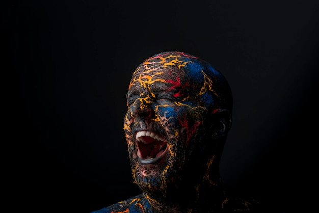Conceptual portrait of a brutal man painted in face art style over black background