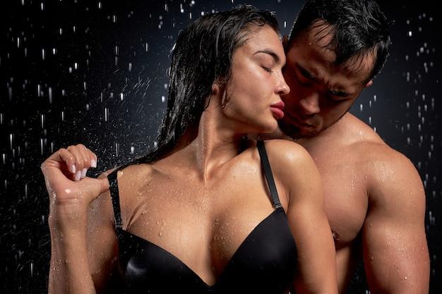 Концептуальный портрет чувственной молодой пары, позирующей под дождем, на черном фоне со светом