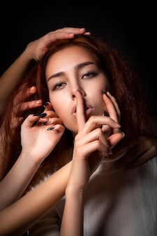 Conceptual portrait of a young woman who holds a finger to her lips as a sign of silence and many people are drawn by knees, stroking and soothing.