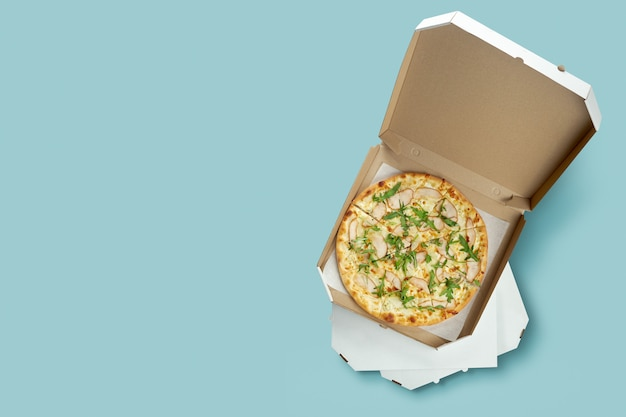 Conceptual poster for food and pizza delivery. meat pizza in a cardboard box for delivery on a blue surface with place for text