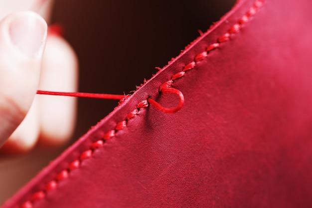Концептуальная профессия таннер. руки женщины сомкнулись вокруг иглы и нити.