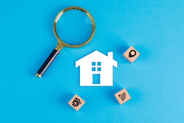 Conceptual of real estate with magnifying glass, wooden blocks, paper home icon on blue table flat lay.
