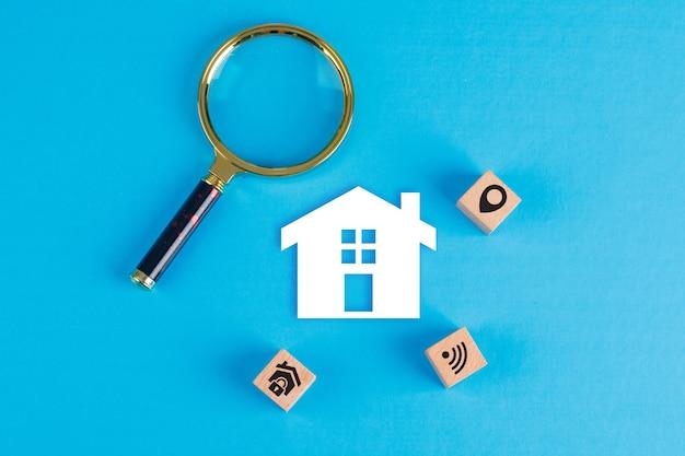 Concettuale di beni immobili con lente di ingrandimento, blocchi di legno, icona domestica di carta sul tavolo blu laici piatta.