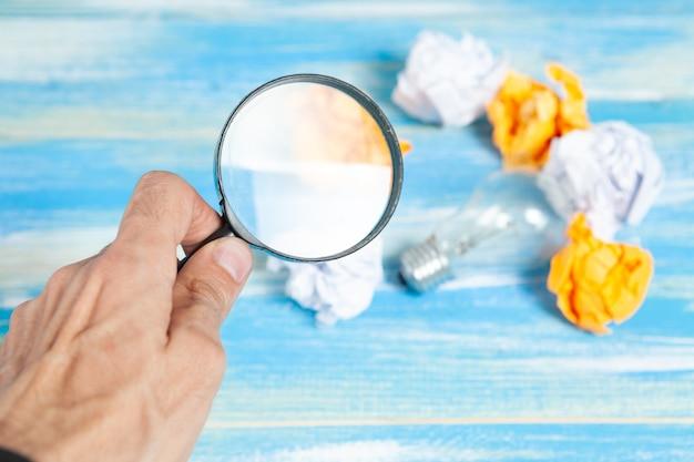 아이디어에 대한 개념적 연구. 램프, 구겨진 종이 및 테이블에 돋보기.