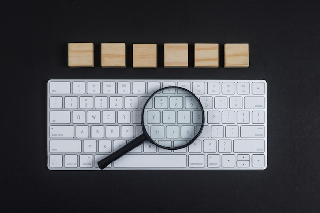 Conceptual of research with keyboard, magnifier, wooden cubes on black desk background flat lay. horizontal image