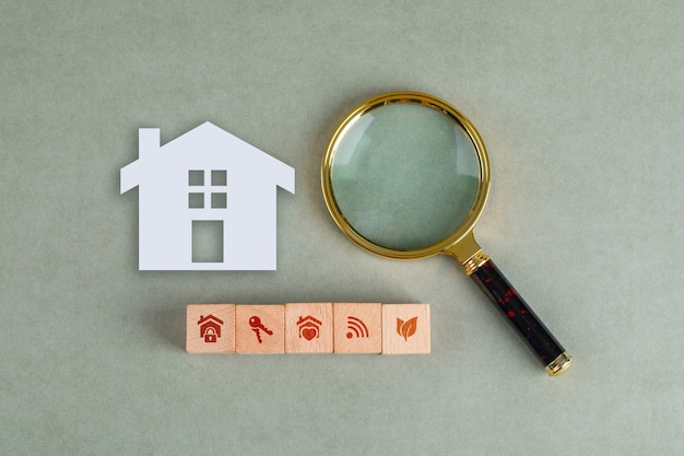 Conceptual of search real estate with wooden blocks, paper home icon and magnifying glass.