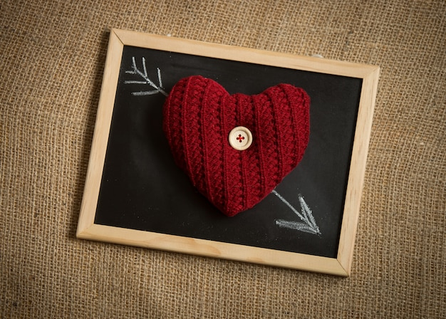 Conceptual shot of knitted heart lying on arrow drawn by chalk