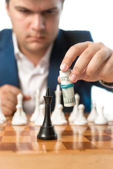 Conceptual shot of money power. man making chess move with dollar banknotes