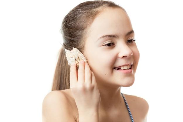 Концептуальный снимок милой девушки, слушающей океан в раковине