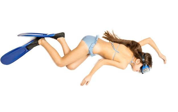 Концептуальный снимок симпатичной девушки, лежащей на полу и делающей вид, что занимается подводным плаванием