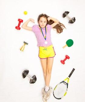スポーツ用品のセットが付いている床に横たわっている女の子の概念的なショット