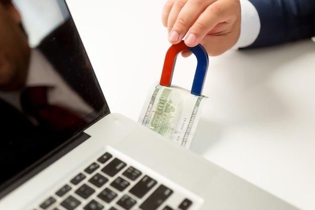 インターネットでお金を盗む概念的なショット。磁石でパソコンのお金を引っ張る男性