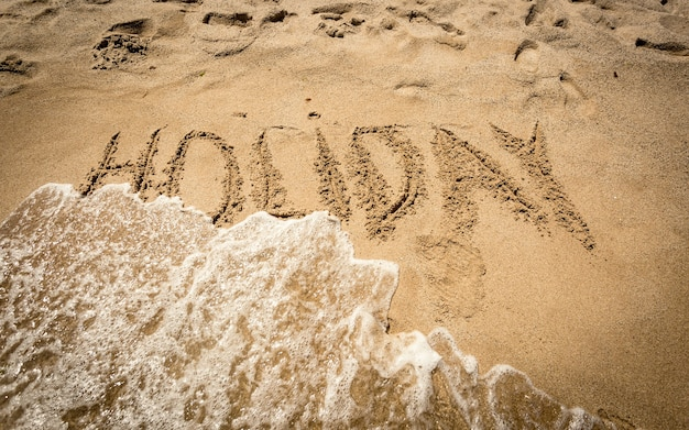 Conceptual shot of word holiday written on sand being washed off by sea wave