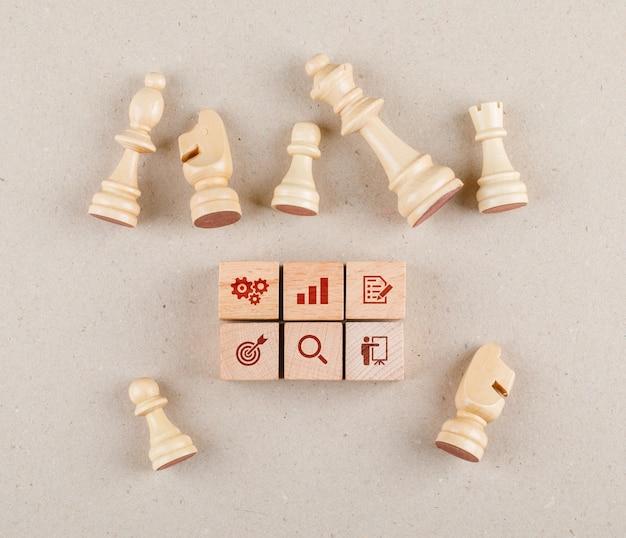 Concettuale della strategia con blocchi di legno con icone, figure di scacchi piatti laici.