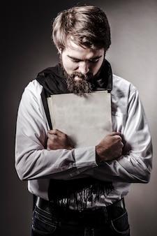Conceptual studio portrait of bearded crazy genius artist, musician or writer embracing his creation