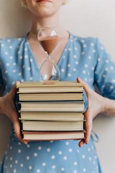 유리 플라스크에 책과 모래 시계를 들고 개념적 시간 여자