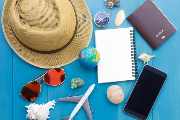 Conceptual tour planing image of travelling accessories on blue wooden background