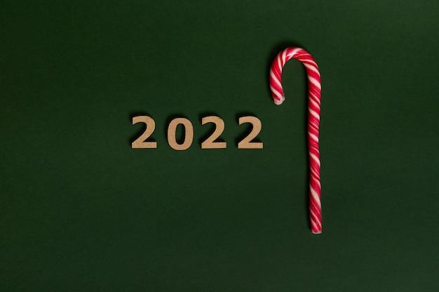 木製の数字2022と甘い縞模様の白と赤のクリスマスロリポップ、甘いキャンディケインの概念的なtudioショット、広告のためのスペースで新年とクリスマスの伝統的なイベントを象徴しています