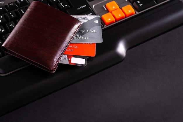 신용 카드, 지갑, 노트북을 사용한 온라인 쇼핑의 개념적 보기.