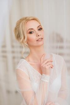 概念的な結婚式、ヨーロッパスタイルの花嫁の朝。 boudoirドレス、インテリアスタジオでの料金。花嫁のための白いミニマリズム