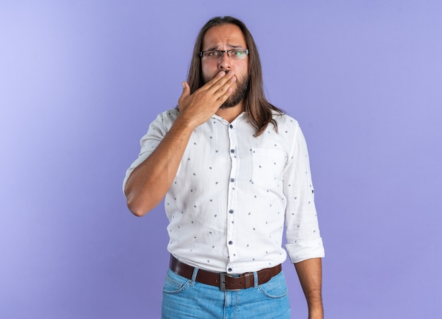Concerned adult handsome man wearing glasses keeping hand on mouth