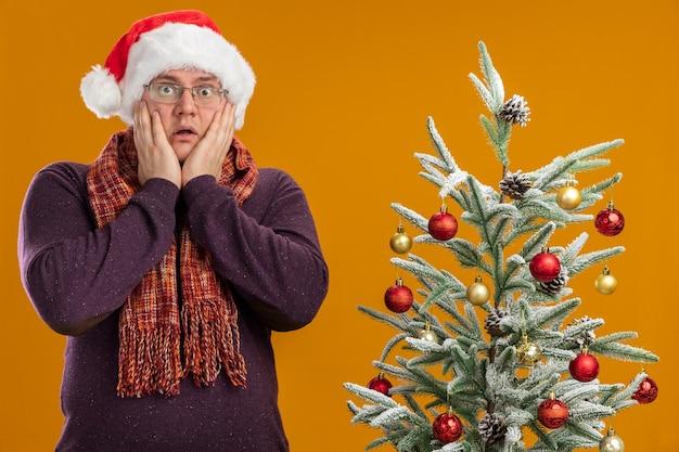 Uomo adulto interessato che indossa occhiali e cappello da babbo natale con sciarpa intorno al collo in piedi vicino all'albero di natale decorato che tiene le mani sul viso isolato sul muro arancione