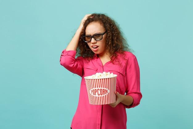 3d 아이맥스 안경을 쓴 걱정스러운 아프리카 소녀가 푸른 청록색 배경에 격리된 머리에 손을 대고 팝콘을 들고 영화 영화를 보고 있습니다. 영화, 라이프 스타일 개념에서 사람들의 감정. 복사 공간을 비웃습니다.