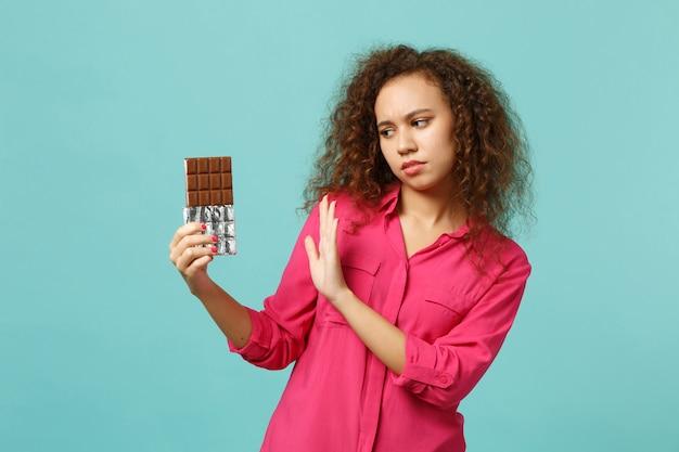 파란색 청록색 벽 배경에 격리된 초콜릿 바에 손바닥으로 중지 제스처를 보여주는 분홍색 캐주얼 옷을 입은 걱정스러운 아프리카 소녀. 사람들은 진심 어린 감정 라이프 스타일 개념입니다. 복사 공간을 비웃습니다.