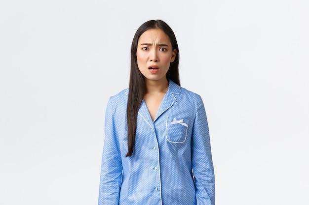 Обеспокоенная и встревоженная молодая азиатская женщина в пижаме, испуганная чем-то тревожным и ужасным, сморщиваясь от разочарования, узнала плохие новости, стоя на белом фоне.