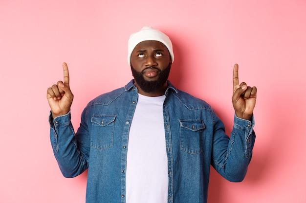 ピンクの背景の上に立って、懐疑的な顔で上を見つめ、指を上に向けるビーニーの心配して躊躇している黒人男性。