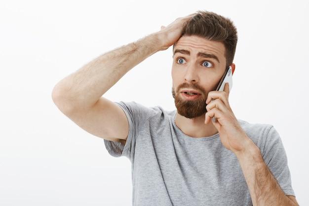 Обеспокоенный и обеспокоенный, встревоженный парень, получивший плохие новости во время телефонного разговора, держит руку на лбу, смотрит влево обеспокоенным и невежественным, стоит в замешательстве и недоумевает над серой стеной
