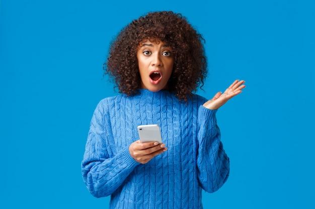 걱정과 충격을받은 젊은 아프리카 계 미국인 여성은 스마트 폰을 통해 불쾌한 소식을 받고, 부끄러운 표정으로 말하고, 으 ging하고 손을 올립니다.