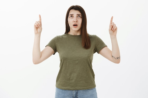 心配して心配している20代の若い女性を指して、口を開けて心配そうに見ている、木に上向きの子猫の神経の安全性