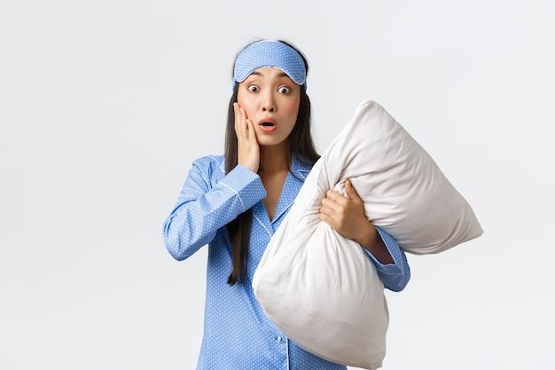 Обеспокоенная и встревоженная молодая женщина в синей пижаме и спальной маске, держащая подушку и задыхаясь, тревожно смотрит, испытывает сочувствие или жалость к кому-то, попавшему в беду, слышит шокирующие новости.