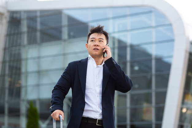 공항 근처에서 통화하는 우려하는 아시아 사업가