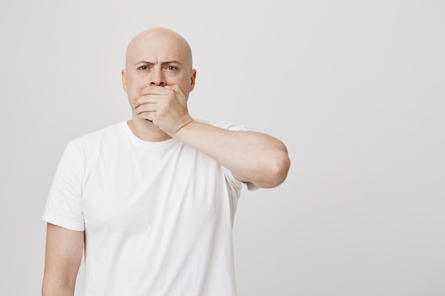 Concerned bald man gasping, cover mouth in shock