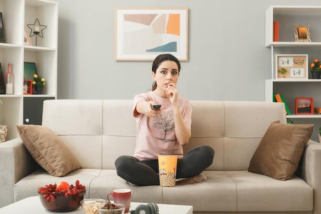 Preoccupato morde le unghie giovane ragazza con il telecomando della tv, seduta sul divano dietro il tavolino da caffè nel soggiorno