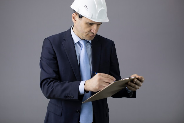 Concerned builder in white helmet and formal clothing writes on clipboard