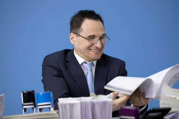 Concerned businessman angrily flips thick stack of accounting records at desk full of paperwork