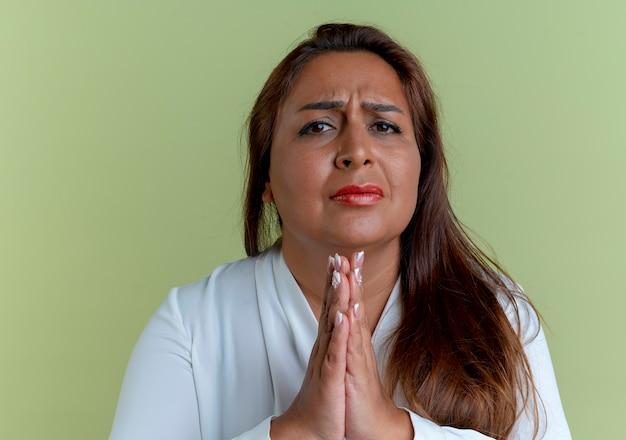 기도 제스처를 보여주는 우려 캐주얼 백인 중년 여성