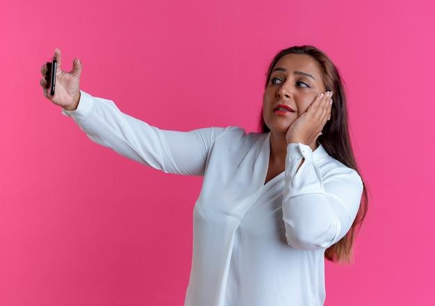 La donna di mezza età caucasica casuale interessata prende un selfie e mette la mano sulla guancia